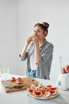 白い壁にグレープフルーツの作品を食べて美しい少女。健康的なフィットネス栄養。コピースペース。