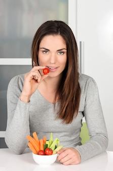 家で健康的な食べ物を食べる美しい少女