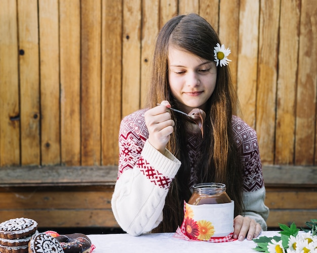 Beautiful girl eating melted chocolate in jar on table