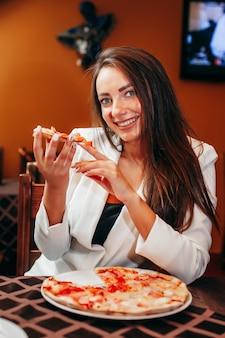 レストランでピザを食べて美しい少女