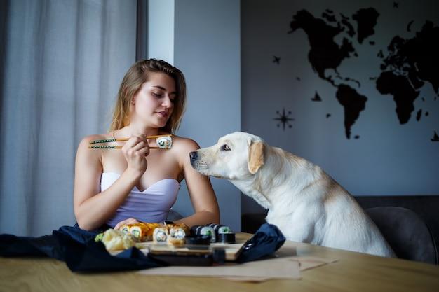 彼女の犬のラブラドールと寿司のクローズアップを食べて、笑顔で、箸で巻き寿司を持っている美しい少女。健康的な日本食。