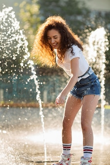 Beautiful girl enjoying her day while playing with water