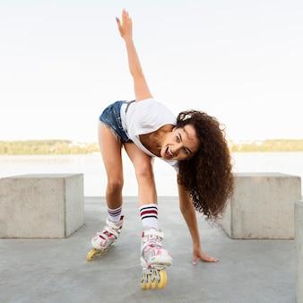 Красивая девушка наслаждается прогулкой на роликовых коньках