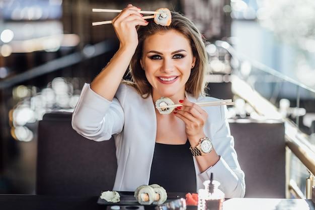 현대적인 카페의 여름 테라스에서 스시를 즐기는 아름다운 소녀.
