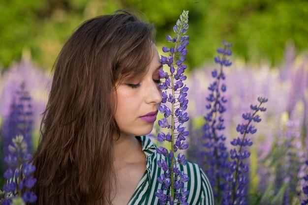 目を閉じた美しい少女は、咲く牧草地のルピナスの花に頭を傾けます