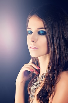 Beautiful girl. fashion makeup, long brown hair and necklace