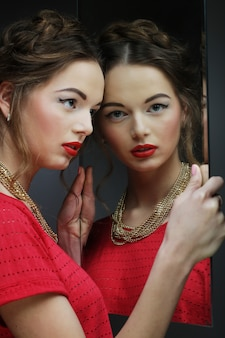 Beautiful  girl female model with bright makeup  and her reflect