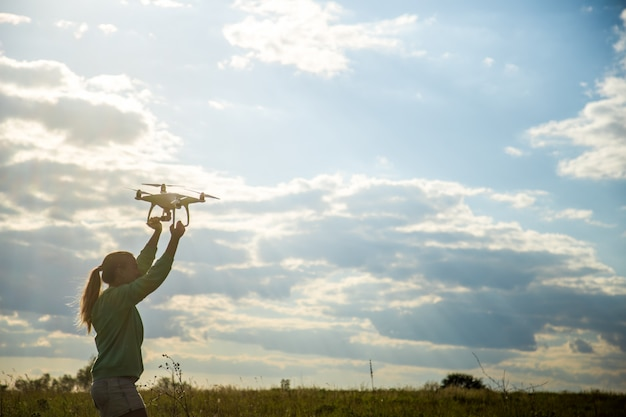 Beautiful girl in a field launches the drone into the sky