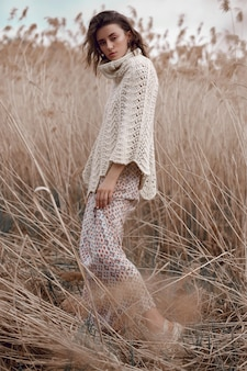 Beautiful girl in a field with tall grass in autumn.