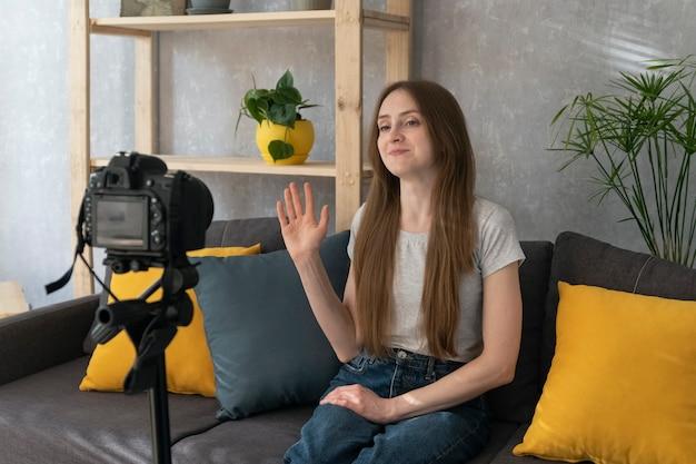 브이로그를 위해 자신을 촬영하는 아름다운 소녀. 젊은 여성 블로거는 카메라에 자신의 비디오를 찍고 손을 흔듭니다.