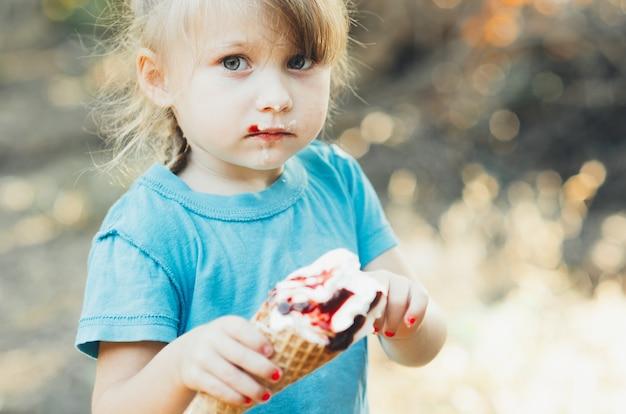 Красивая девочка пяти лет ест мороженое на природе, рог с фруктами