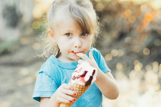 Beautiful girl five years eating ice cream in nature, the horn with fruits