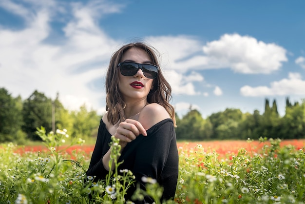 Beautiful girl on the flowers field, sunny day. summer time