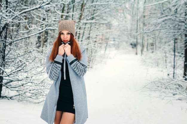 Beautiful girl freezes in the winter in the forest. photo in cold tones