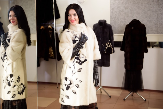 The beautiful girl in a fur coat in the store measures and chooses clothes