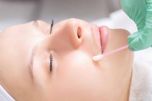 Beautiful girl gets face peeling. skin health concept. beauty salons. mixed media