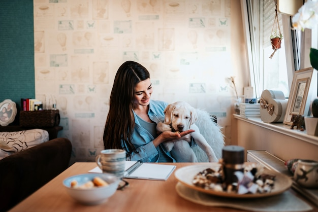 Beautiful girl giving a treat to her dog at home.