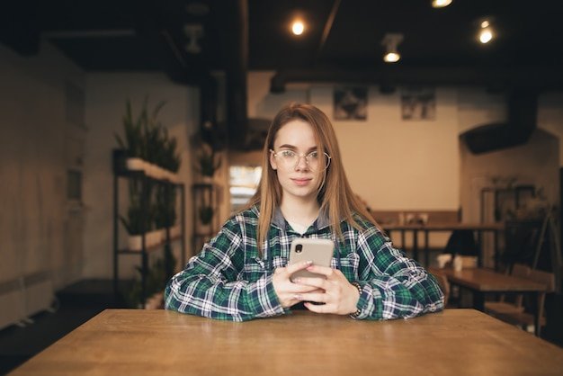 Beautiful girl in glasses and casual clothes sitting at the table in a cozy cafe, holding a smartphone in the hands, looking into the camera