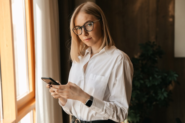 A beautiful girl in glasses stands by the window in the office in her hands with a phone typing text.