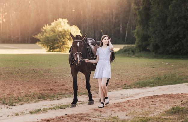 美しい少女は馬と一緒に道路に行きます