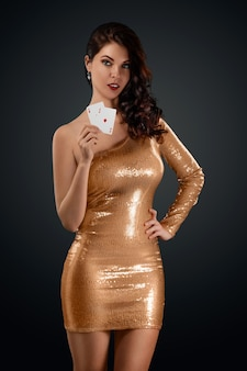 Beautiful girl in a gold shiny croupier dress holds in her hand two playing cards