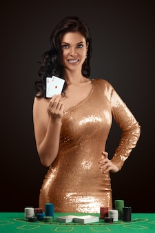 A beautiful girl in a golden shining croupier dress holds in her hand two playing cards in front of her