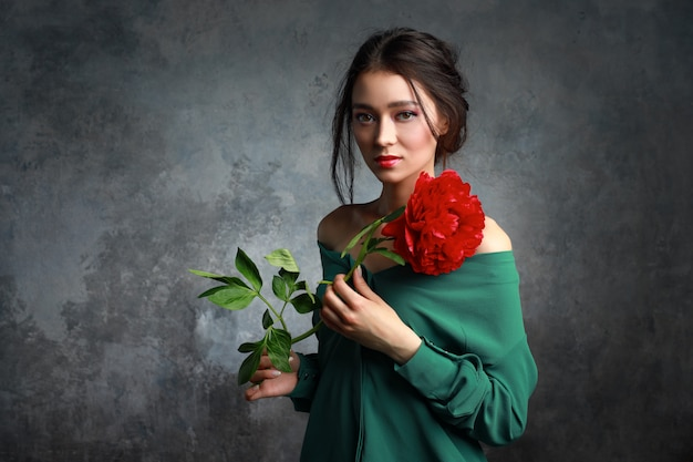 Beautiful girl in the green dress with flowers peonies in hands on a light gray background. joyful asian female model posing in studio with bouquet of spring flowers