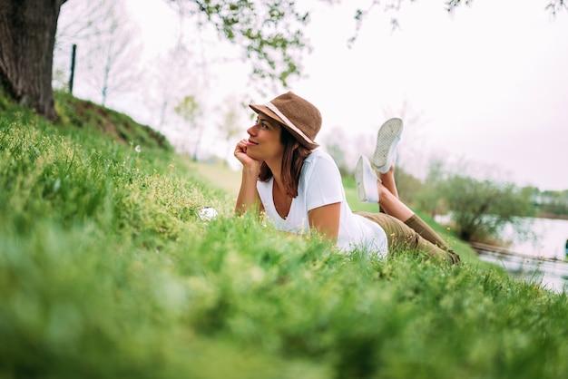 Beautiful girl on green grass laying and enjoying beautiful day.