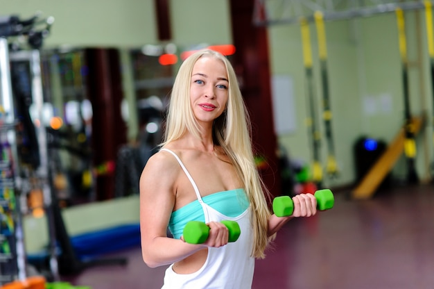 Beautiful girl at the gym, is engaged with dumbbells