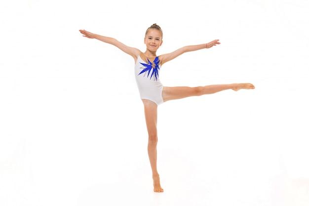 タイツの美しい少女体操は白で隔離されるいくつかの演習を行う