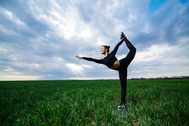 緑の芝生の上の美しい女の子の体操選手はヨガをします。緑の芝生の上の美しい若い女性は、アクロバティックな要素を実行します。黒の柔軟な体操選手は分割で逆立ちを行います