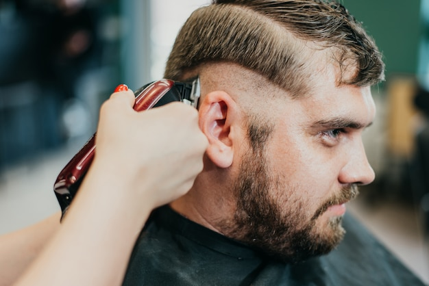 Beautiful girl hairdresser cuts a bearded man in the salon