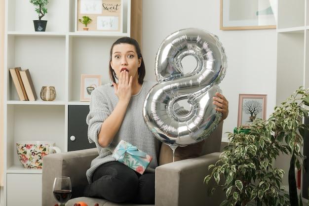 Bella ragazza nel giorno delle donne felici che tiene il palloncino numero otto seduto sulla poltrona in soggiorno