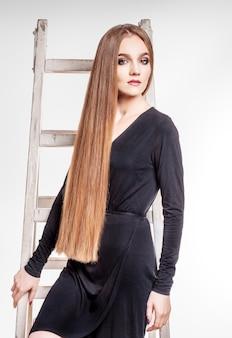 Красивая девушка имеет очень длинные здоровые волосы.