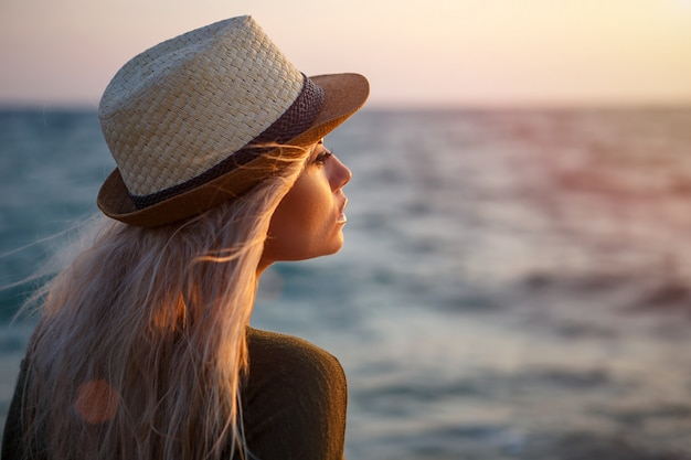 Beautiful girl in hat by the sea at sunset.