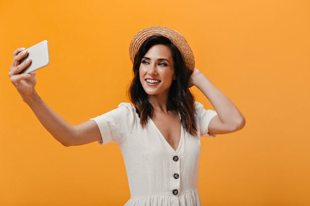 Beautiful girl in hat happily makes selfie on orange background. charming smiling woman in light fashionable dress makes photo.