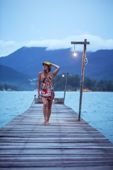 Beautiful girl in hat on the longest wooden pier in the evening on koh chang, thailand