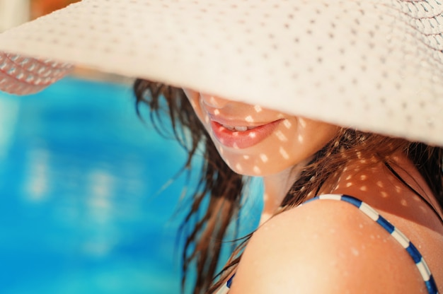 Beautiful girl in a hat relaxing near a swimming pool