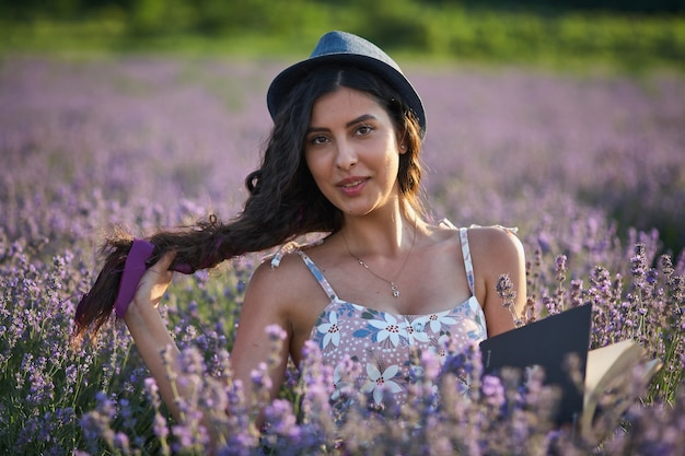 Beautiful girl in hat sitting in purple lavender field and read book.