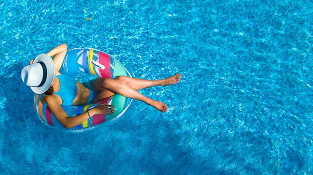 Beautiful girl in hat in swimming pool aerial top view from above, young woman relaxes and swims on inflatable ring donut and has fun in water on family vacation, tropical holiday resort