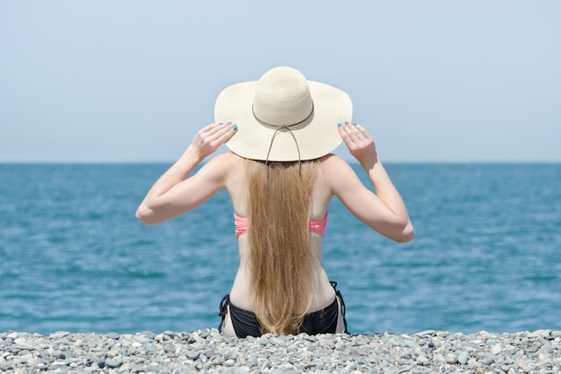 Beautiful girl in a hat and swimsuit sits on the beach. sea on the background. view from the back
