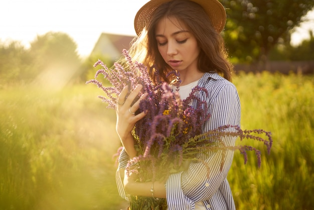 A beautiful girl in a hat with a bouquet of lavender. she is dressed in a blue shirt, a white t-shirt and a hat.