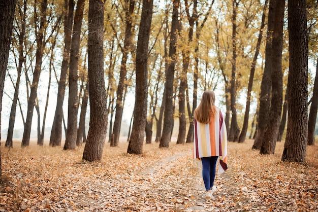 자연의 아름다움에 감탄하는 가을 숲에서 산책하는 아름다운 소녀