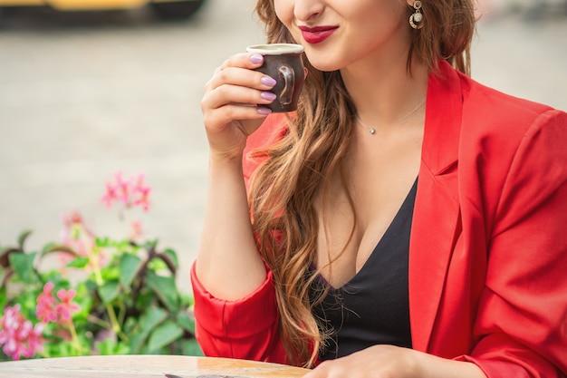 Красивая девушка с кофе в кафе на открытом воздухе.
