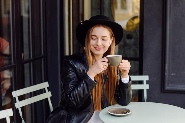 カフェでコーヒーを飲んでいる美しい少女