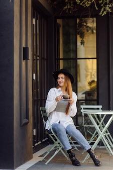 Bella ragazza che mangia caffè al caffè