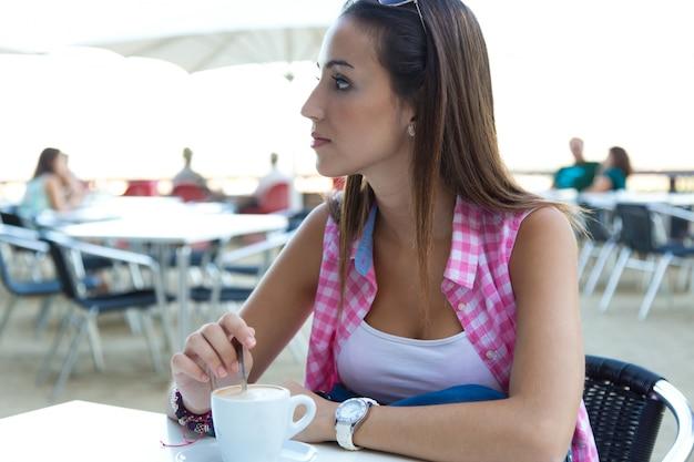 Beautiful girl having coffee on the street.