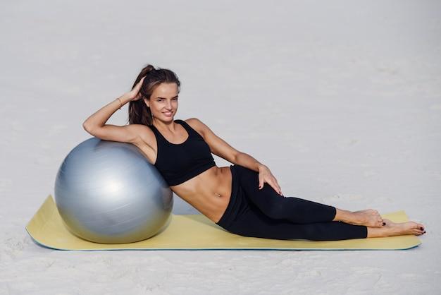 日の出や日没のビーチでフィットネスボールと残りの部分を持つ美しい少女。フィットネススポーツヨガと健康的なライフスタイルのコンセプト。