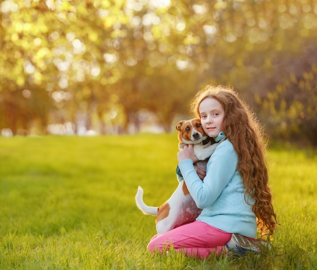 Beautiful  girl and her cute dog  embracing in spring outdoors.