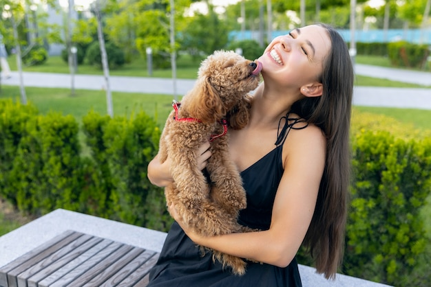 Beautiful girl and her pet little golden poodle dog strolling in public park outdoors